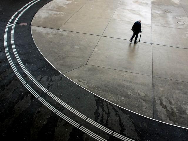 Ein Mann auf einem Bahnhofplatz.