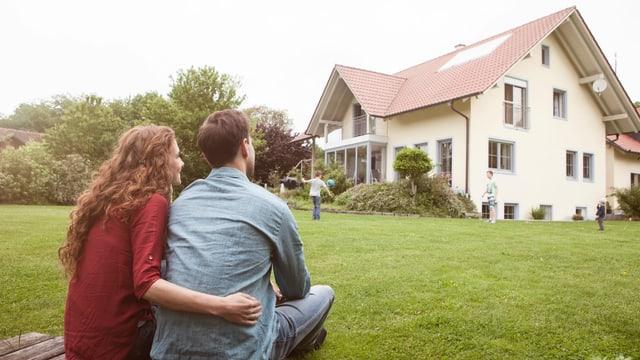 Frau und Mann schauen ein Haus an