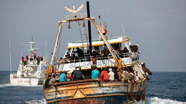 Ein afrikanisches Schiff wird von der italienischen Küstenwache begleitet