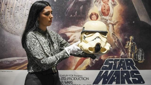 Eine Frau mit Handschuhen hält einen weissen Helm. Im Hintergrund hängt ein Star-Wars-Plakat.