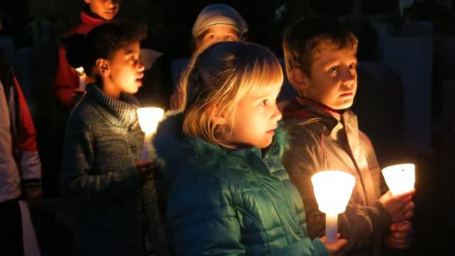 Schulkinder singen an einem Grab.