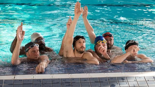 Eine Gruppe Männer in einem Schwimmbecken streckt die Hände nach oben.