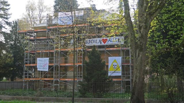 Ein Haus mit Baugerüst und bunten Transparenten.