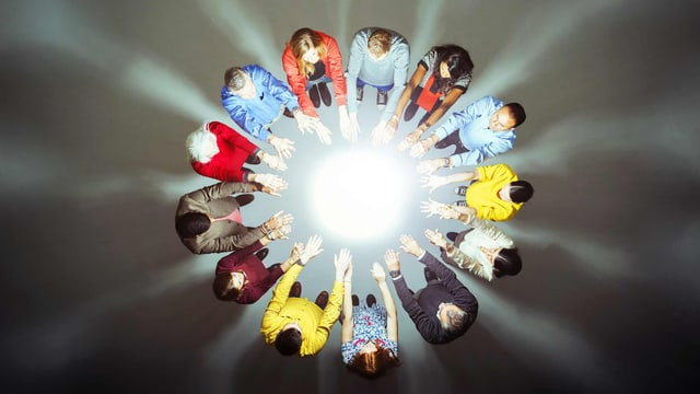 Menschen im Kreis die Hände zum Leuchtpunkt in der Mitte gerichtet.