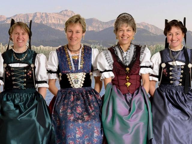 Die vier Musikantinnen tragen Appenzeller Trachten und sitzen in einer Bildcollage am Ufer eines Sees.