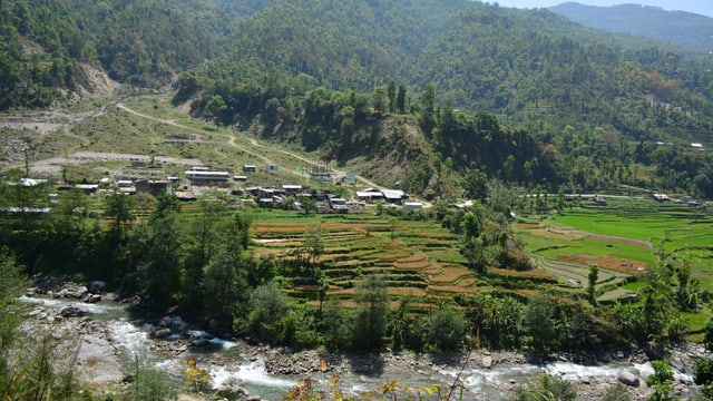Dorf in der Ferne, grüne Umgebung, im Vordergrund ein Fluss.