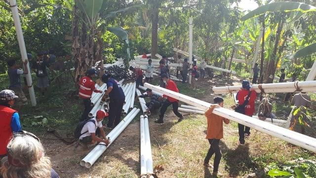 Voluntaris e spezialists dad autras branschas gidan ils teams da la Crusch Cotschna Indonaisa da reparar l'infrastructura d'aua e d'electricitad.