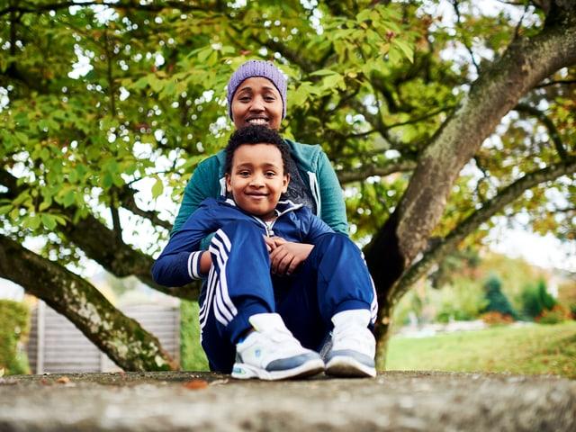 Eine Mutter umarmt ihren Sohn, der auf einem Fels sitzt.