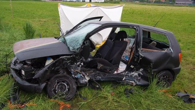 Ein Auto steht total beschädigt, ohne Türen, in einer Wiese.