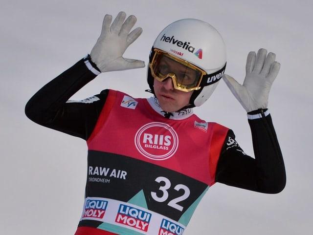 Simon Ammann nach der Landung mit beiden Handflächen in der Luft und abwinkend
