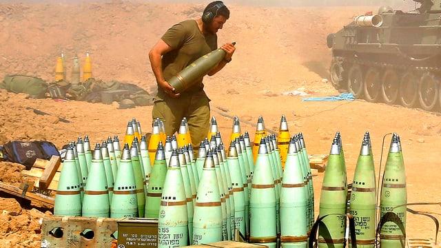 Ein israelischer Soldat lagert Panzer-Raketen neben einem Panzer der israelischen Armee.