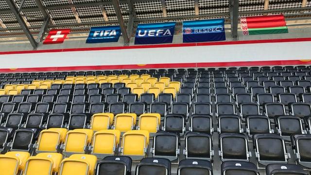 Schware und gelbe Sessel auf einer Fussballtribüne