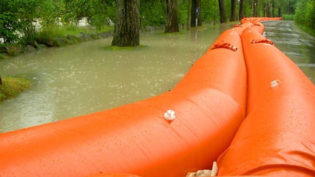 Bild vom «Beaver» im Einsatz: Gelbe, grosse Plastikschläuche wurden mit Wasser gefüllt und liegen entlang eines überfluteten Bachlaufes am Wegrand und verhindern, dass Wasser auf den Weg läuft.