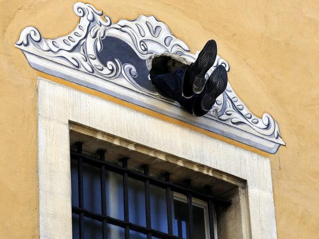 Zwei Füsse schauen aus einem Loch in der Fassade über einem Fenster heraus