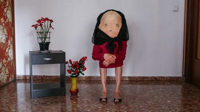 Eine Person mit vornübergebeugtem Rücken, auf dem ein Gesicht gemalt ist, steht in einem kirchenähnlichen Innenraum.