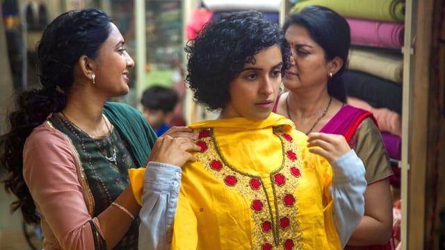 Eine indische Frau im Kleiderladen: sie hält ein Kleid vor sich hin und steht vor einem Spiegel.