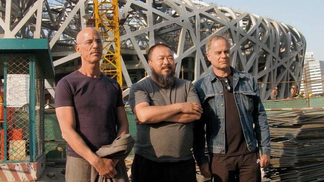 Herzog & De Meuron mit Ai Wei Wei vor einem Gebäude.