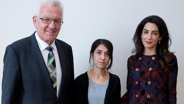 Nadia Murad (mez) a chaschun d'in inscunter a Stuttgart cun Winfried Kretschmann ed Amal Clooney.