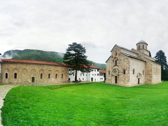 Klostergebäude mit Kirche umgeben von Wiesen und Bäumen.