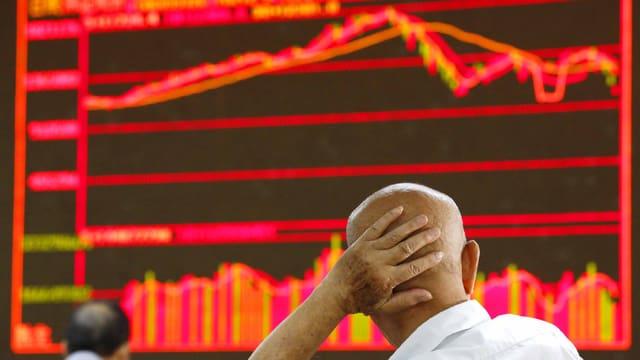Mann, der seine linke Hand an den Hinterkopf hält, Börsenkurse im Vordergrund, Aufnahme von hinten.