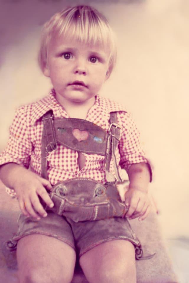 Kleiner Junge posiert mit Lederhosen