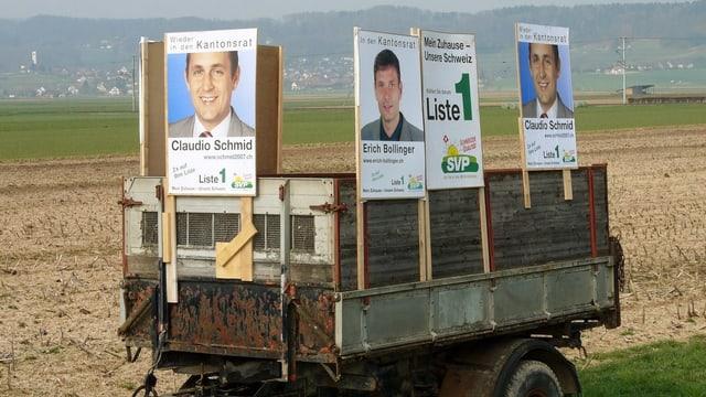 Anhänger auf einem Feld mit Wahlplakaten