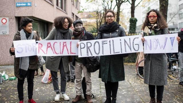 """Vier Frauen und ein Mann halten ein Transparent hoch, darauf steht """"Stop Racial Profiling Now"""""""