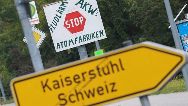 Deutscher Wegweiser nach Kaiserstuhl, Schweiz, im Hintergrund ein Protestplakat gegen Fluglärm, AKW und Atomfabriken