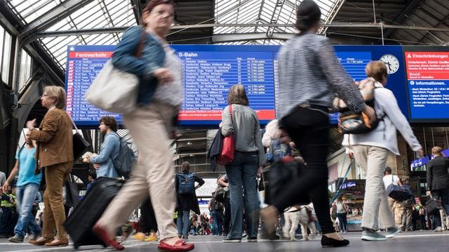 Reisende im Bahnhof Zürich bewegen sich vor der grossen Anzeigetafel in der Haupthalle
