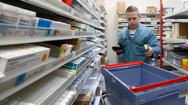 Ein Mann in blauem Kittel steht zwischen Regalen mit Medikamentenpackungen, ein blauer Plastikbehälter steht neben ihm auf einem Rollgestell.