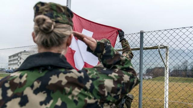 Soldatin salutiert vor Schweizer Flagge