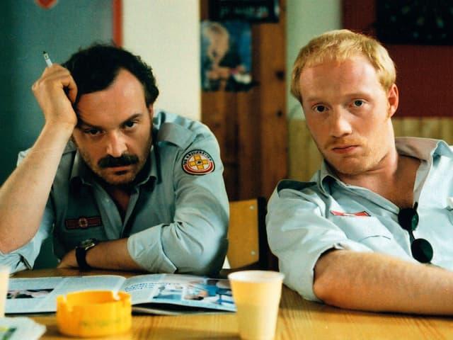 Filmszene: Brenner und Berti sitzen an einem Tisch, sie tragen die Uniformen von Krankenwagenfahrern.