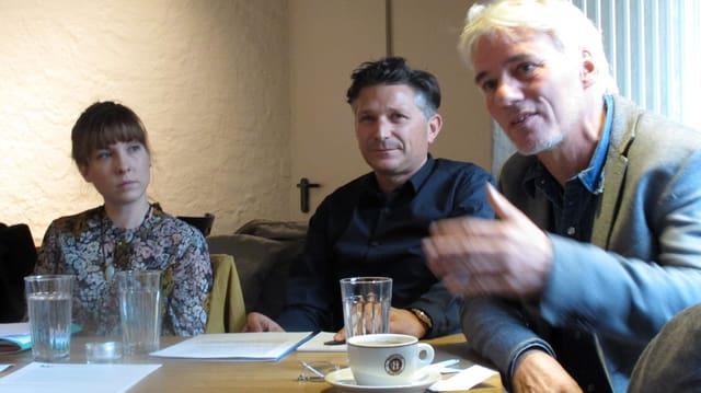 Eine Frau und zwei Männer präsentieren an einem Tisch ihre Ziele.