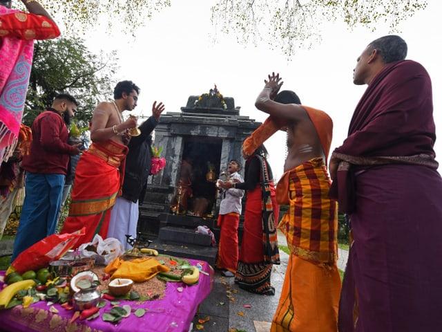 Eine Gruppe von Menschen steht vor einem kleinen Tempel aus Stein.
