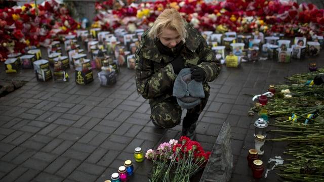 Eine Frau trauert, legt Blumen neben Kerzen auf dem Maidan-Platz.