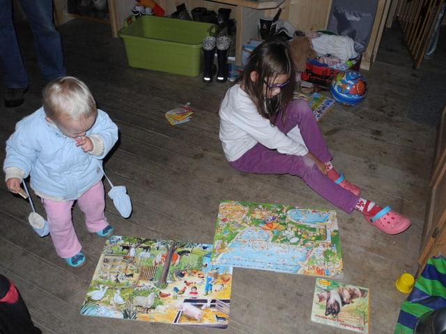 Die beiden Mädchen spielen auf dem Holzboden der Alphütte.