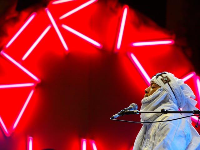 Der Trommler ist weiss gekleidet. Im Hintergrund leuchtet die rote Schrift: Afrika.
