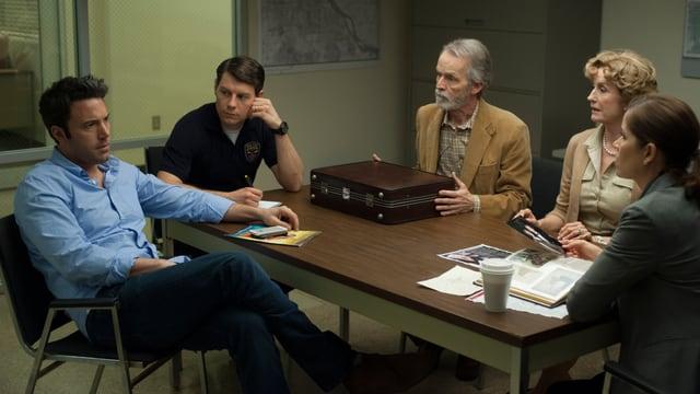 Die Polizei führt Ermittlungen zu einem Fall. Alle sitzen um einen Tisch.