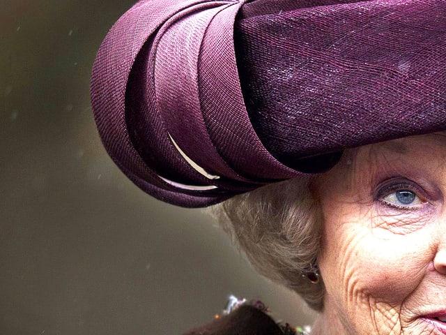Portrait der Hälfte des Gesichts der Königin Beatrix von Niederlanden. Ihr Blick ist kühl und durchdringend zugleich.