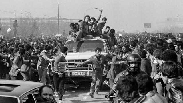 Menschenmenge jubelt Mann in Auto zu.