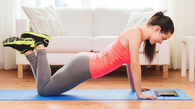 Eine Frau macht eine Fitnessübung und schaut dabei auf ein Tablet.
