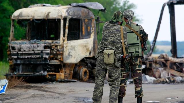 Zwei prorussische Aktivisten betrachten ein Lastwagen-Wrack, Aufnahme von hinten