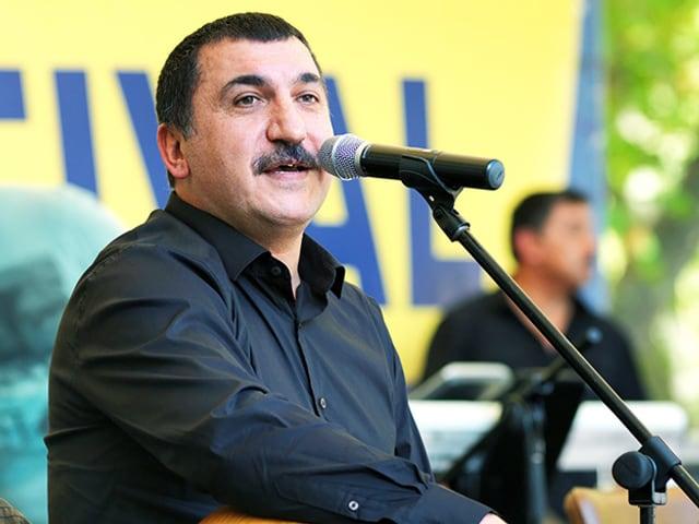 Mann mit Schnauz und kurzen Haaren vor einem Mikrofon.