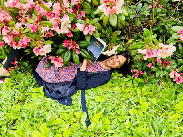 Annette liest den Krimi «River Clyde» von Simone Buchholzer und liegt dabei unter dem Rhododendronbusch