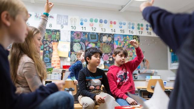 Schulklasse, Kinder sitzen in Gruppen und strecken auf.