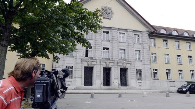Ein Mann mit Kamera vor dem Bezirksgericht Zürich.