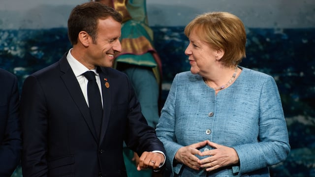 Eine Frau und ein Mann stehen einander gegenüber. Die Frau formt mit den Händen eine Raute, der Mann macht eine Faust.