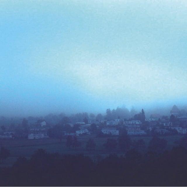 Eine Wolke hängt tief über einem Dorf, das Sonnenlicht kann man nur noch schwach erkennen.