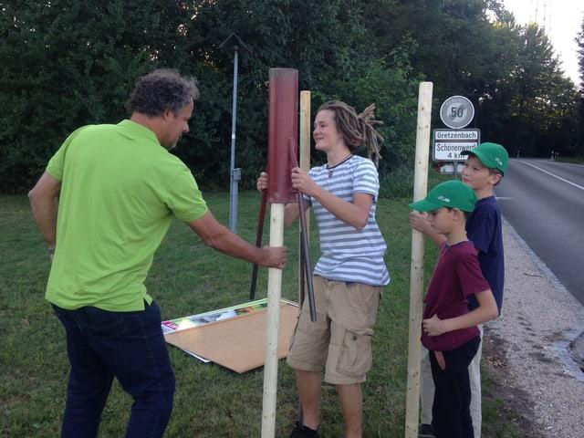 Martin Bossard und seine Söhne bei der Arbeit (stellen Wahlplakate auf)