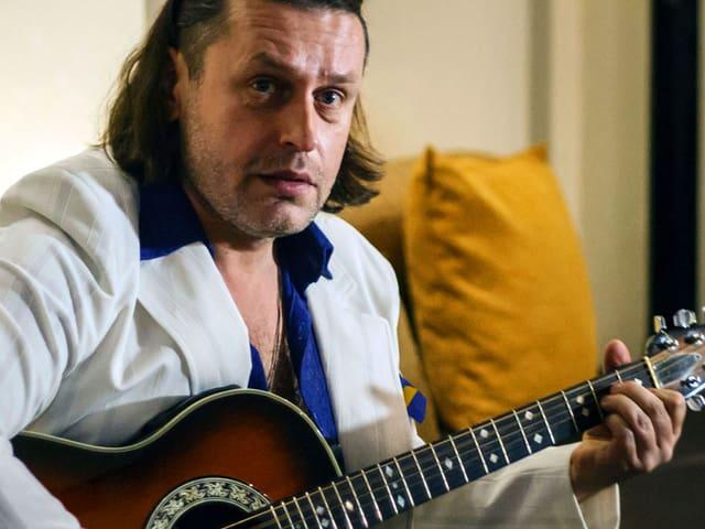 Ein Mann mit kinnlangem Haar sitzt auf einem Sofa und spielt Gitarre.